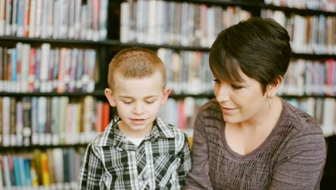 Woman showing a boy something in the book
